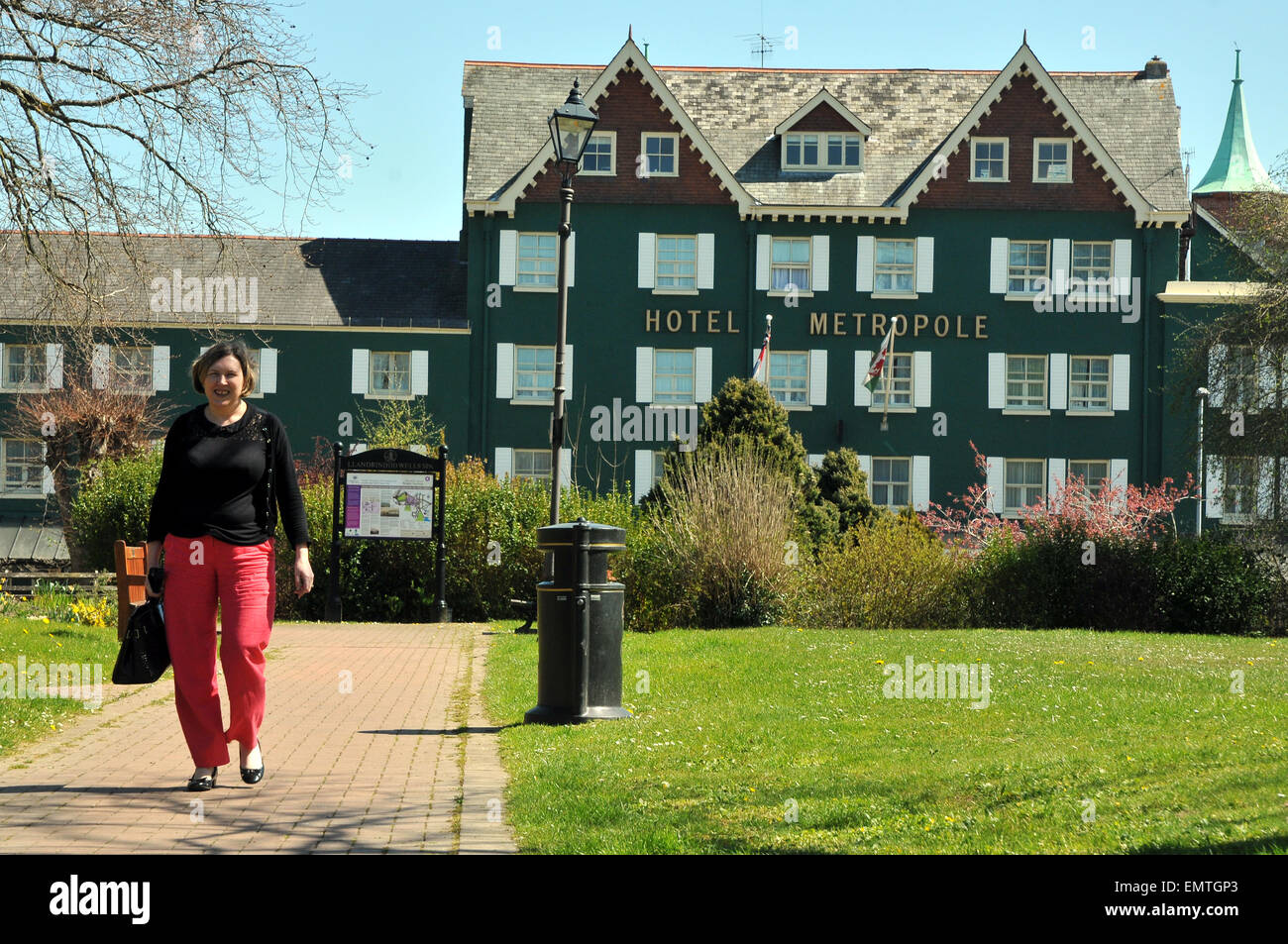 A woman walking to work in front of the Metropole Hotel in Llandrindod Wells - Stock Image