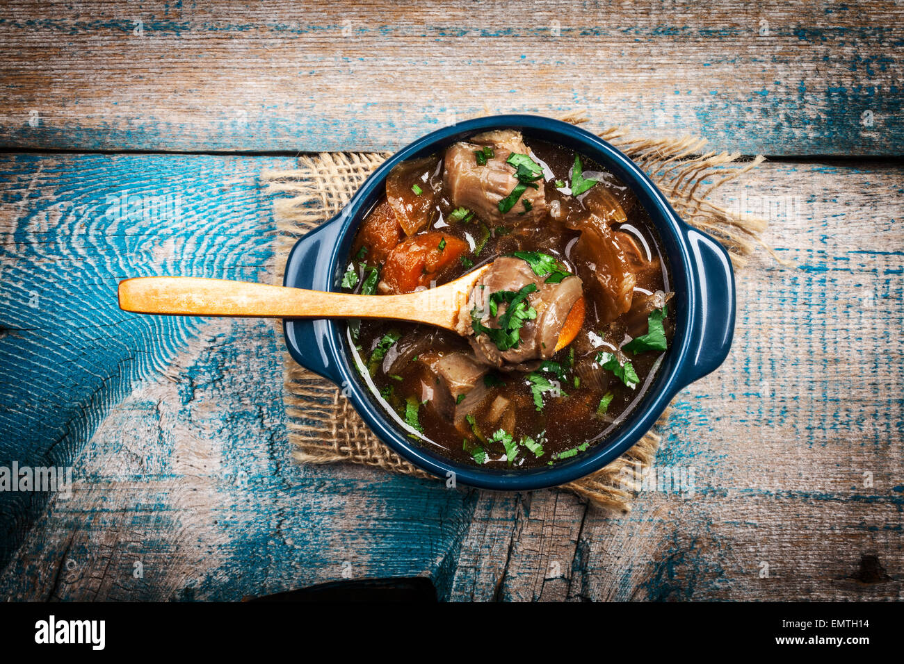Meat stew with vegetables and herbs on old wooden table - Stock Image