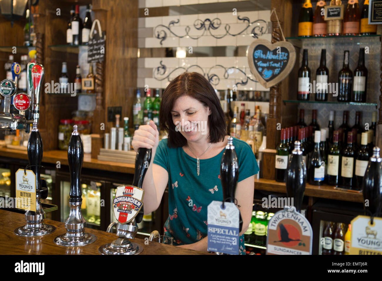A barmaid pulling a pint in a pub - Stock Image
