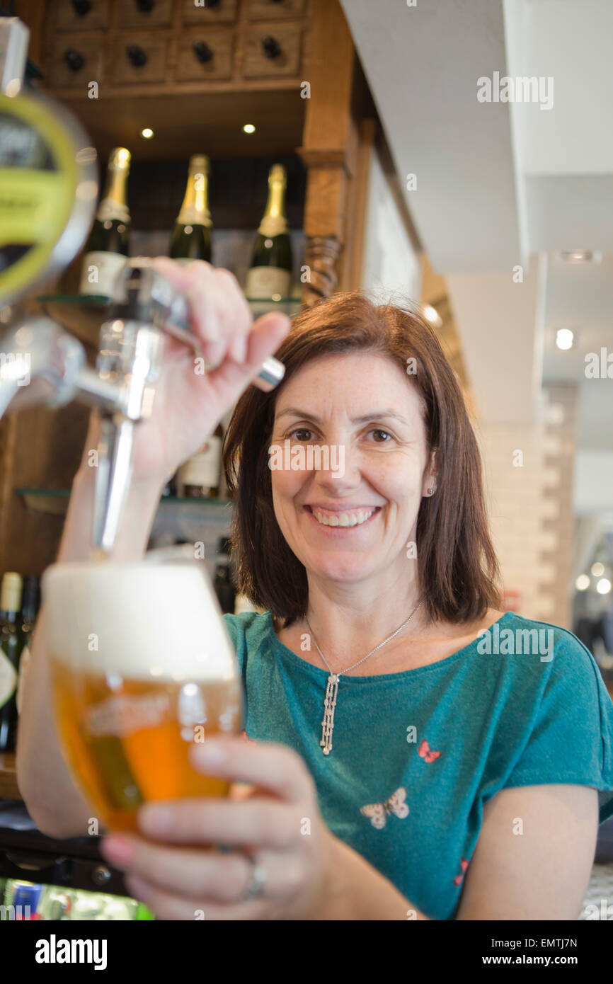 A woman behind a bar pulling a pint of lager while smiling - Stock Image