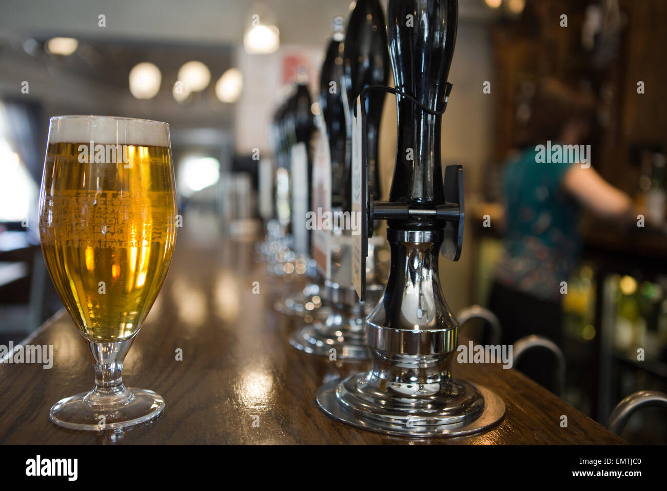 A pint of lager in a pub with a member of staff behind the bar - Stock Image