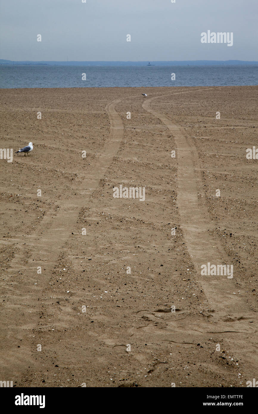 Tire tracks in the sand at the beach at Coney Island on the Atlantic Ocean in Brooklyn, NY. - Stock Image