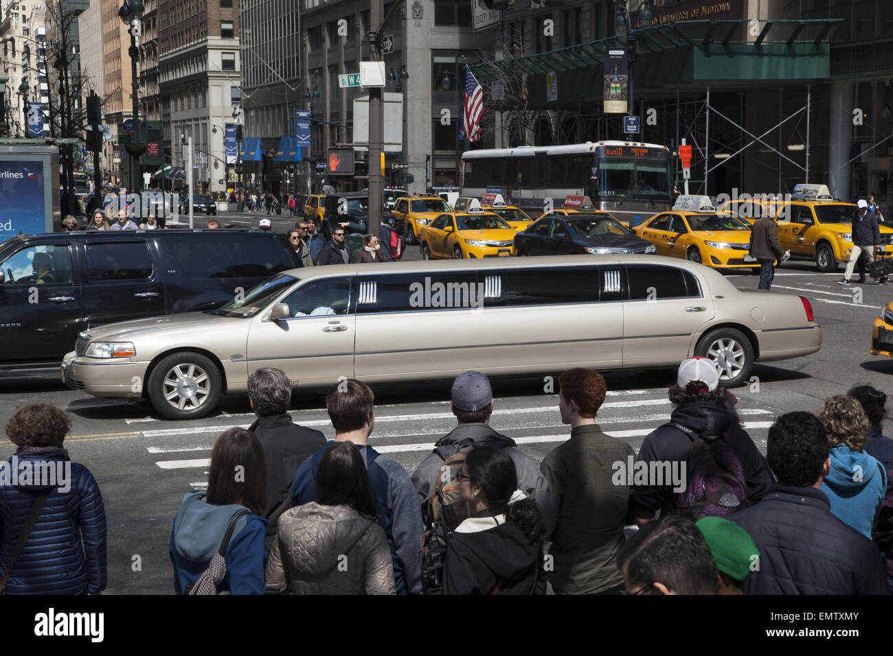 A stretch limousine crosses 5th Ave on 42nd St., a corner that is always crowded with pedestreians. - Stock Image