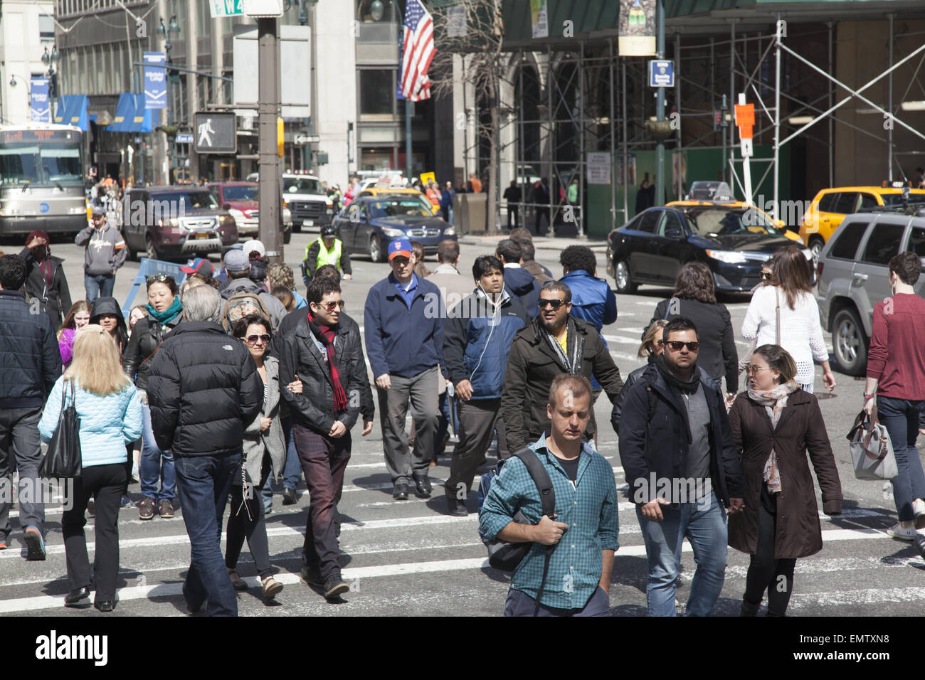 The always busy corner of 5th Avenue and 42nd Street in midtown Manhattan on a sunny spring day. - Stock Image