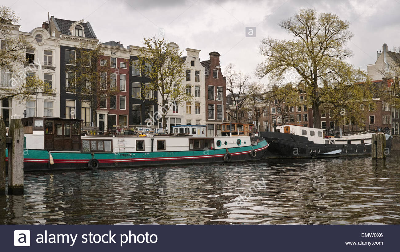 Houseboats and period buildings fronting the River Amstel: Amsterdam, The Netherlands. - Stock Image