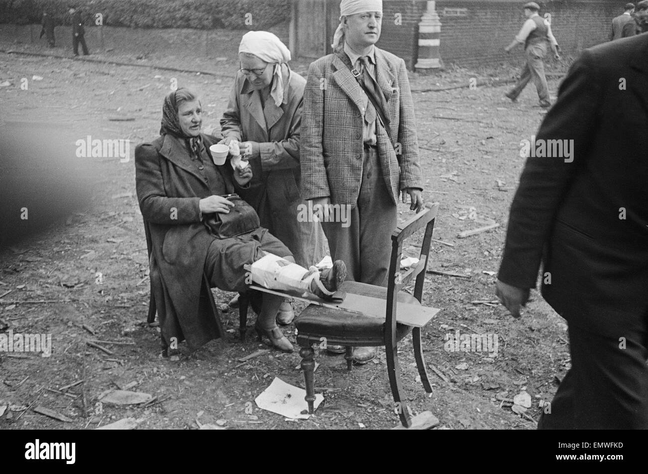 Injured woman drinking a cup of tea after air raid. - Stock Image