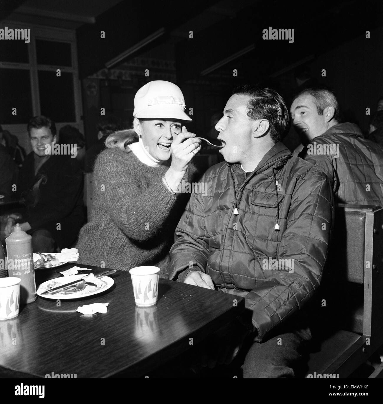 A hungry Jim Clark Racing Driver competing in the 1966 RAC Rally around Britain is fed a couple of chips by fellow Stock Photo