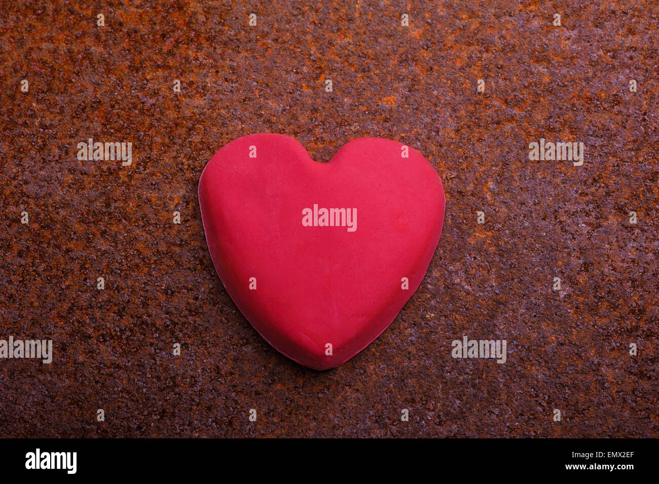 Imperfect, handmade fondant icing heart.on a corroded, rusty background. - Stock Image
