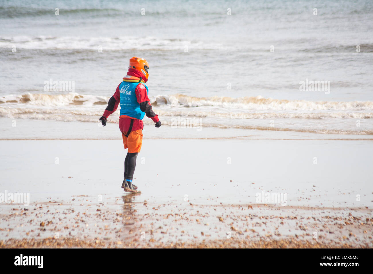 Man in helmet and safety gear walking into the sea  for the ThunderCat Racing UK at Boscombe beach, Dorset, UK in - Stock Image