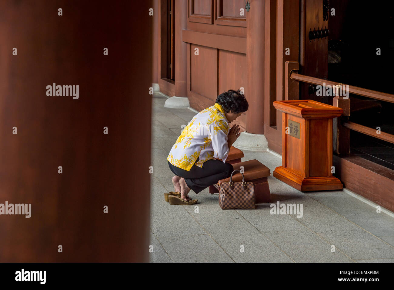 Chinese Woman praying in a monastery in Hong-Kong - Stock Image