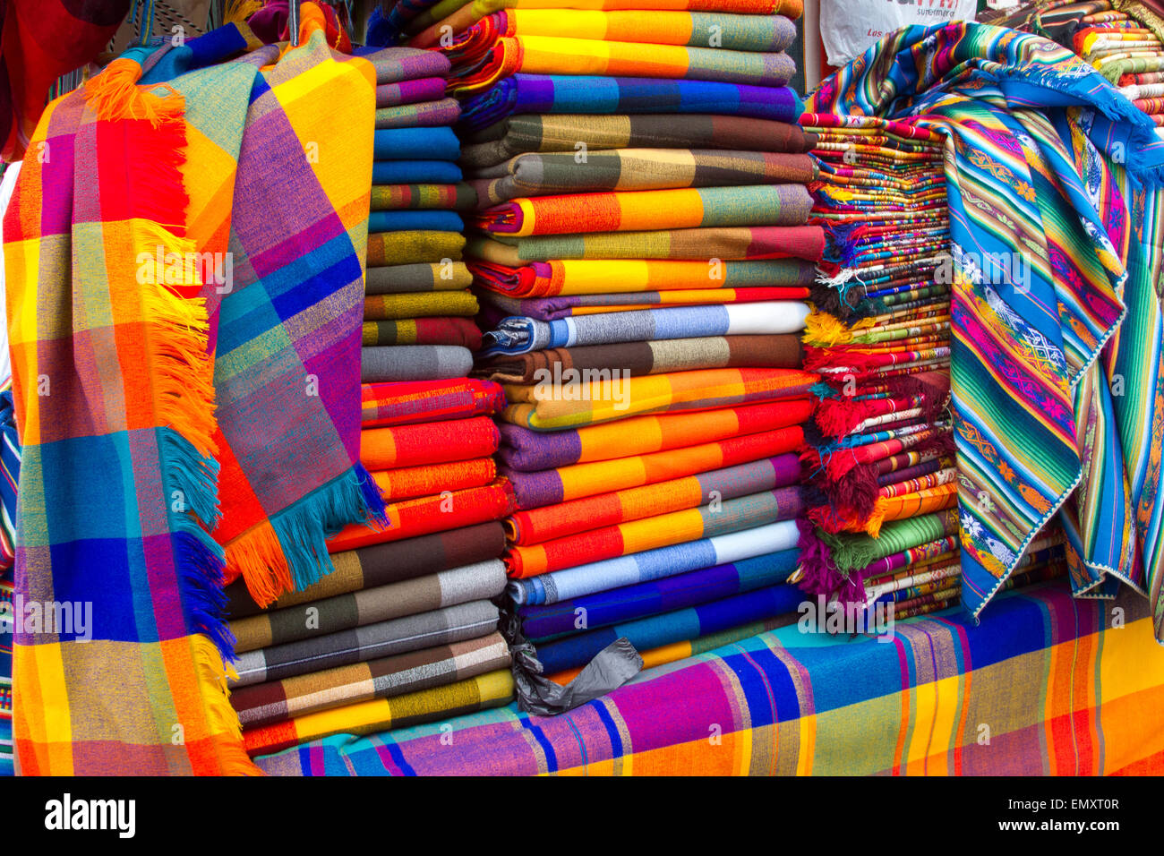 Brightly colored fabrics on display for sale at Otavalo market, Ecuador - Stock Image