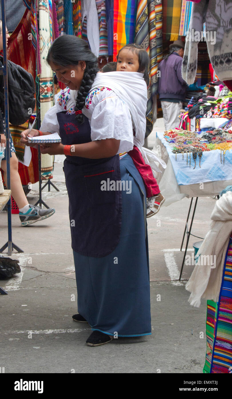 Woman with child selling at Otavalo market, Ecuador - Stock Image