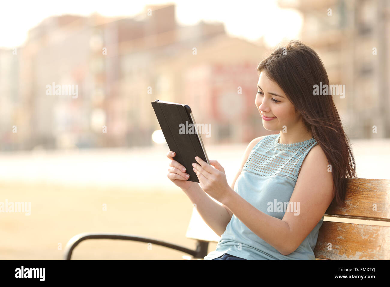 Happy teen student girl reading a tablet or ebook and learning in a park - Stock Image