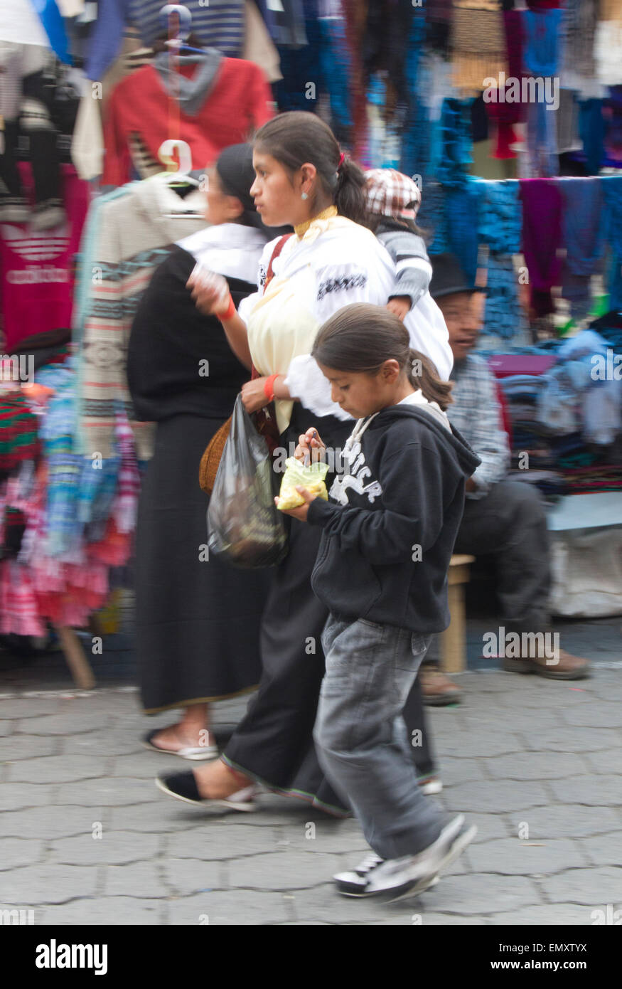 Shoppers walking through marketplace at Otavalo market, Ecuador - Stock Image