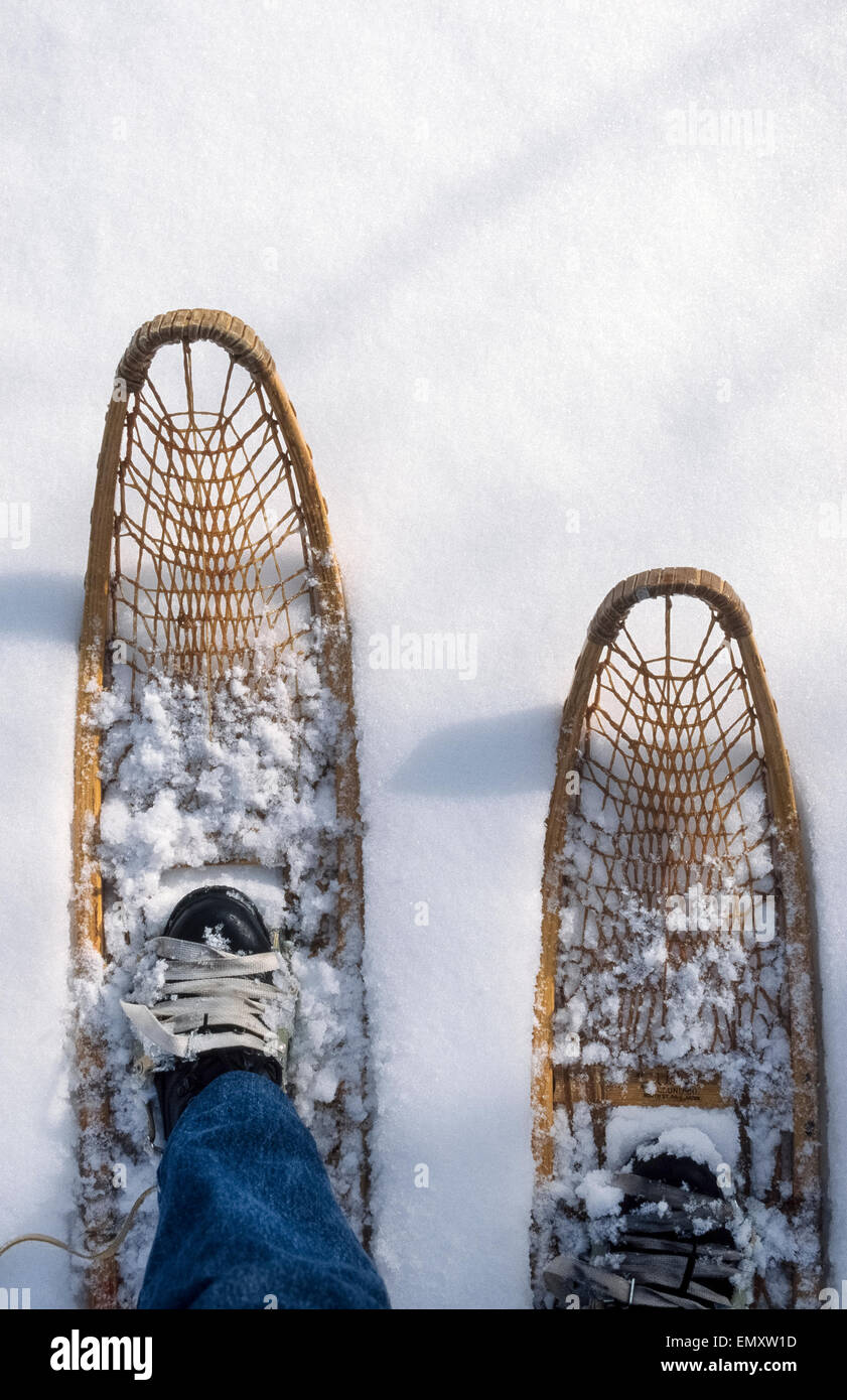 A man wearing old-fashioned traditional wood-frame snowshoes treks over pristine snow during a wintertime visit - Stock Image