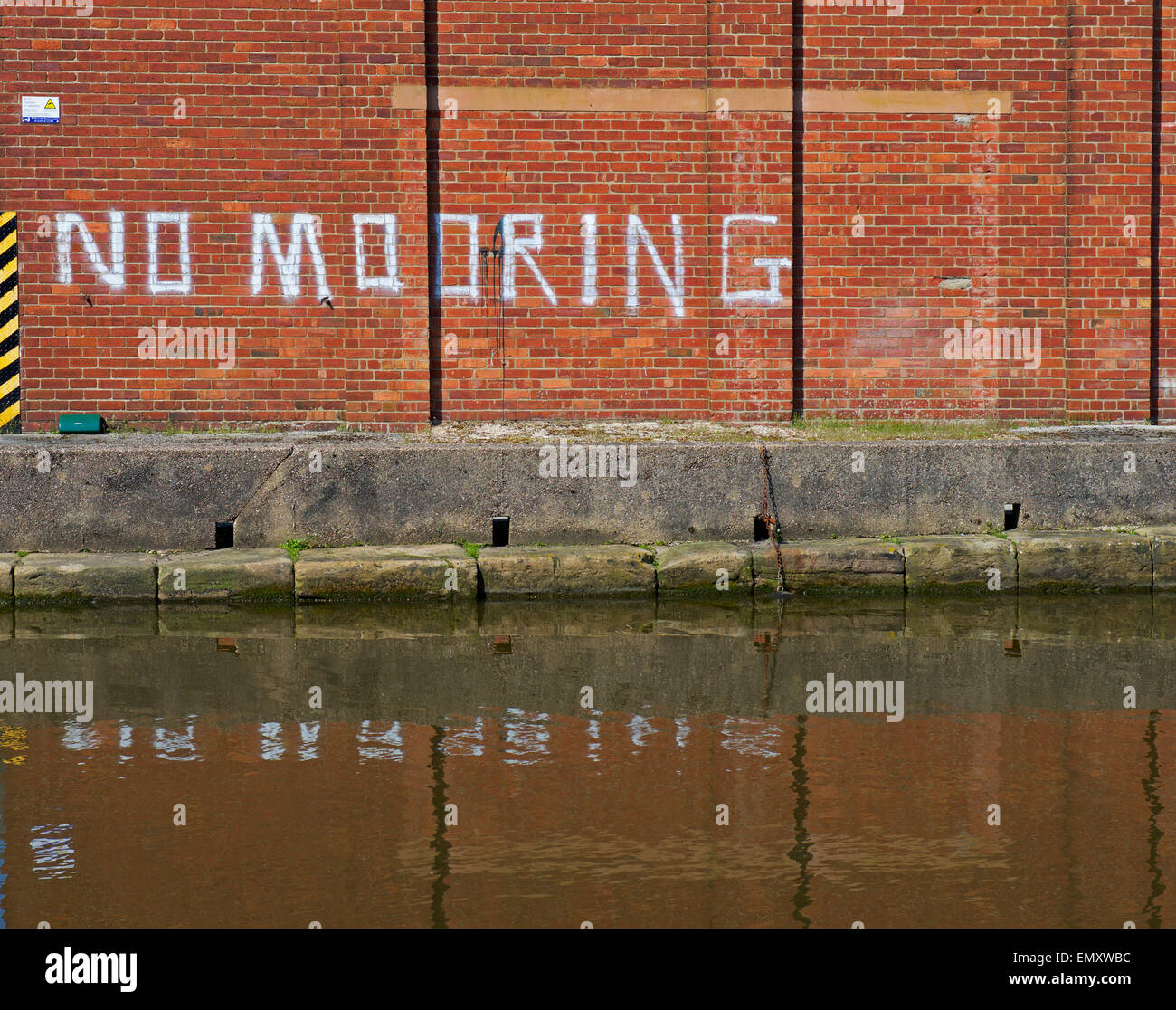 Sign - no mooring - on brick building next to canal, England UK - Stock Image