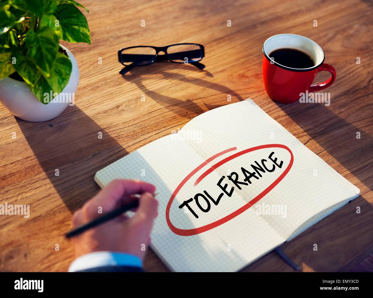 Businessman Writing the Word 'Tolerance' - Stock Image
