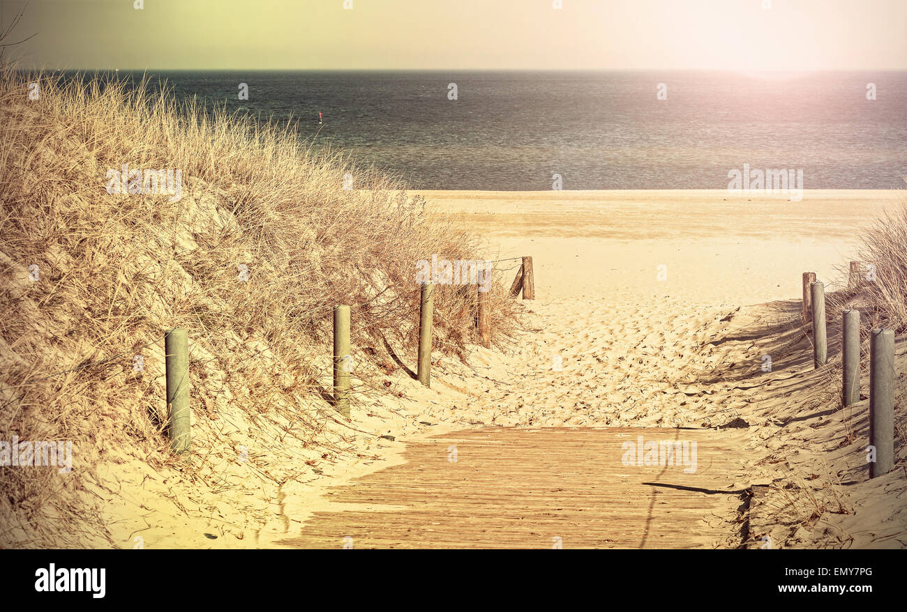 Retro toned panoramic photo of a beach path, old film filter applied. Stock Photo