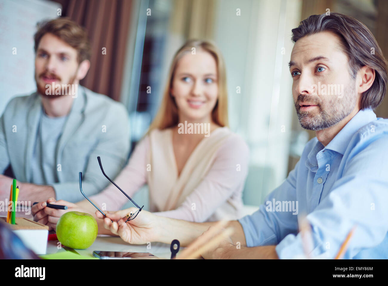 Confident businessman debating with co-worker at meeting - Stock Image