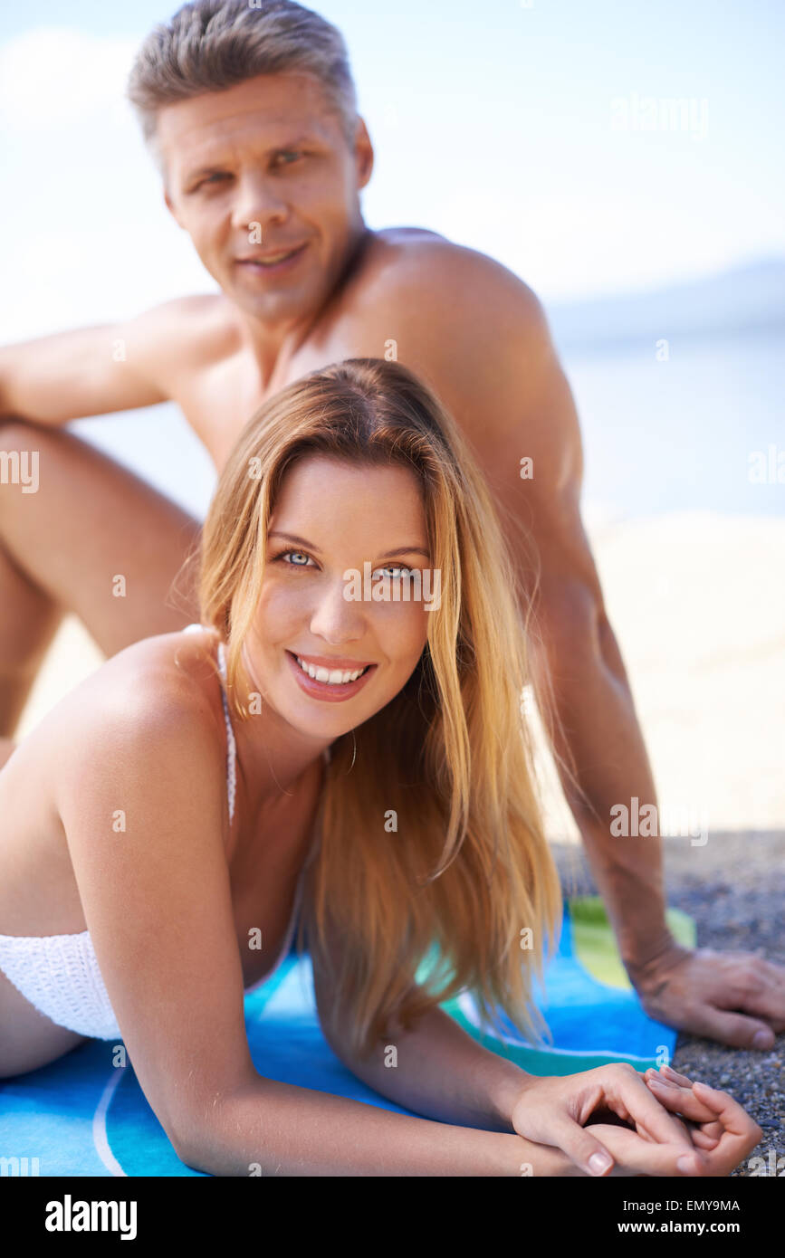 Happy young couple sunbathing at summer resort - Stock Image