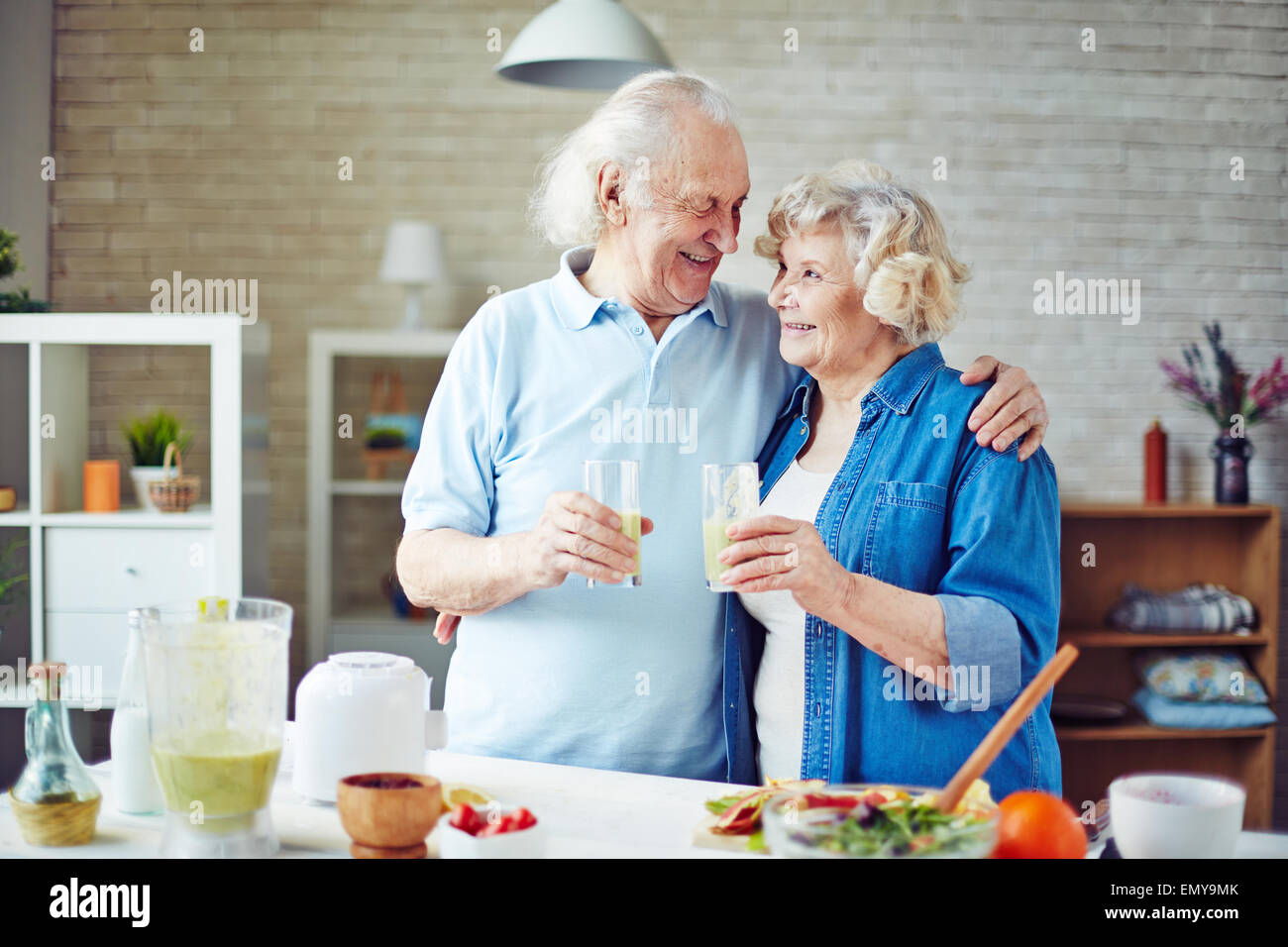 Cheering seniors with glasses of fresh smoothie - Stock Image