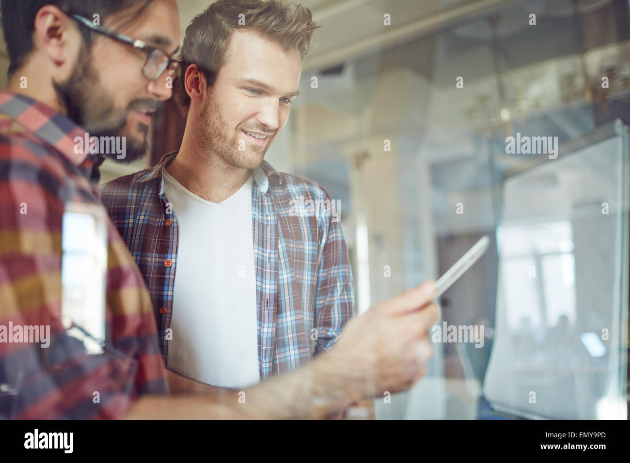 Modern businessmen with touchpad consulting at meeting in office - Stock Image