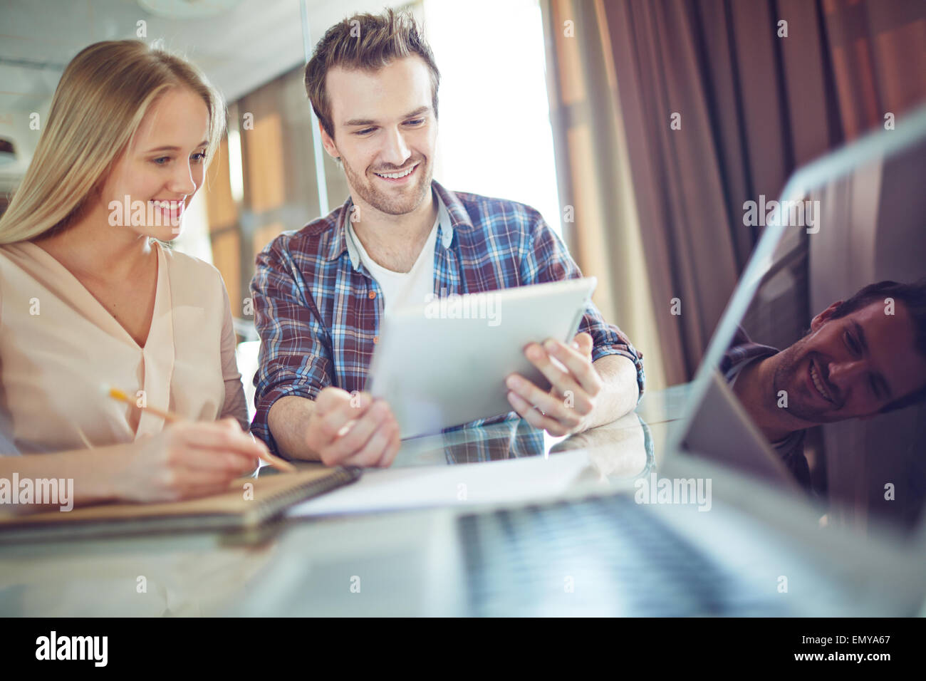 Young employees looking through data in touchpad at meeting - Stock Image