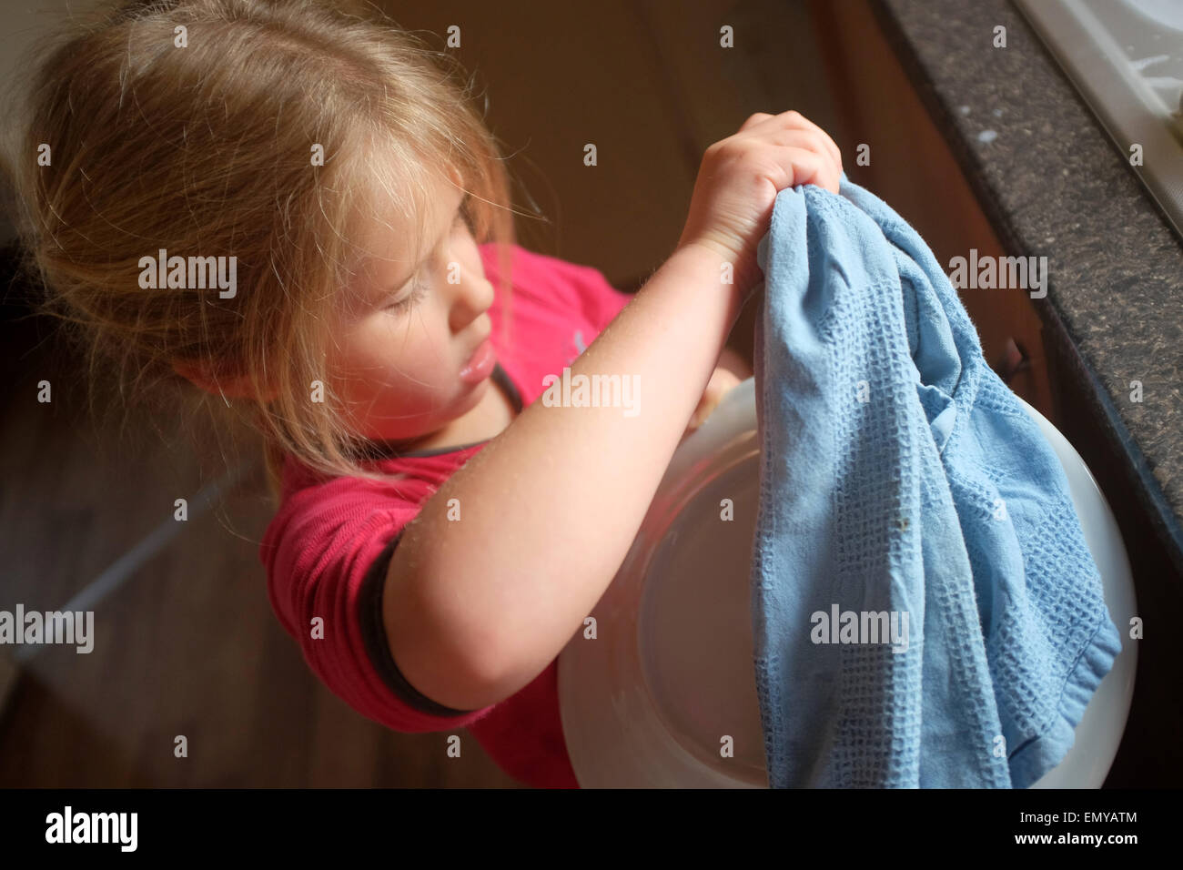 A young girl washing up and drying dishes - Stock Image