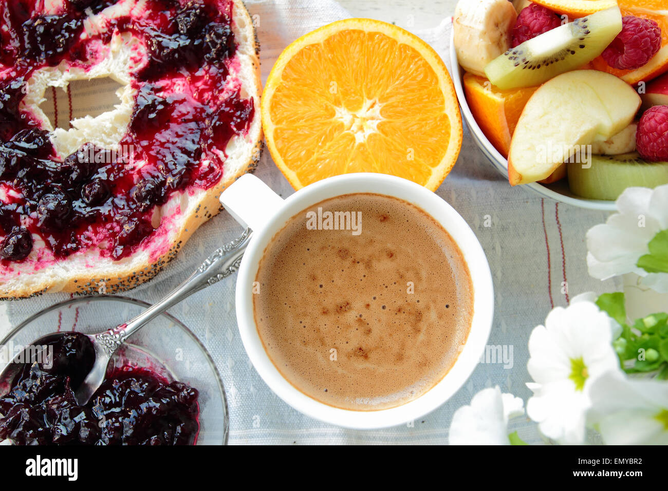 Breakfast with bread with currant jam, coffee and fruits - Stock Image