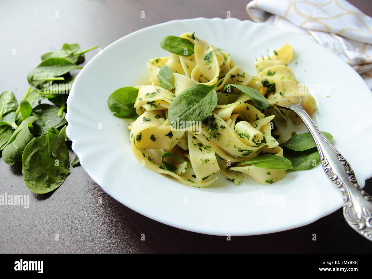 Pasta pappardelle with spinach leafs on white plate - Stock Image