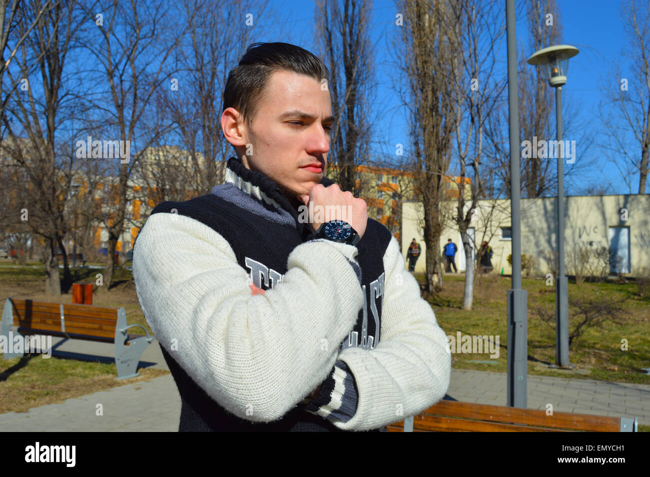 Young man profile with wristwatch on his hand in park - Stock Image