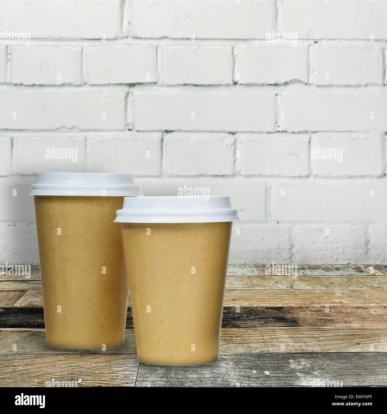 Takeaway coffee cups on wooden table against brick wall backgrou - Stock Image
