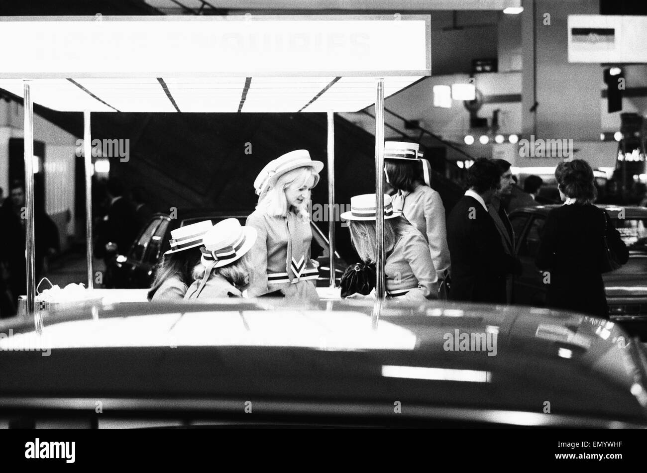 Some of the stall attendants on the Lancia stand at the 1972 Motor Show at Earls Court seen here having a chat. - Stock Image