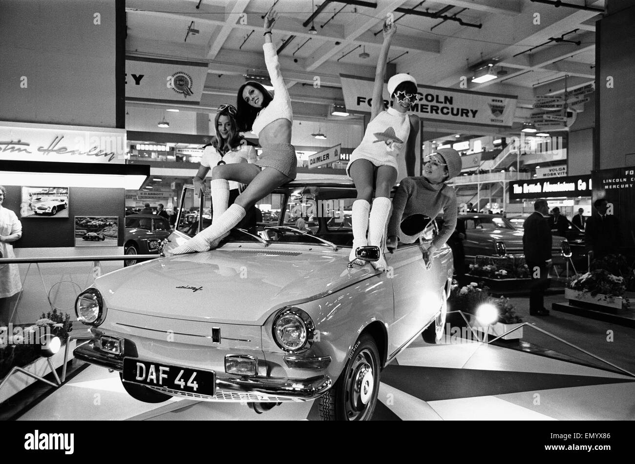Models drapped over a DAF 44 car at the London Motor Show 18th October 1966. - Stock Image