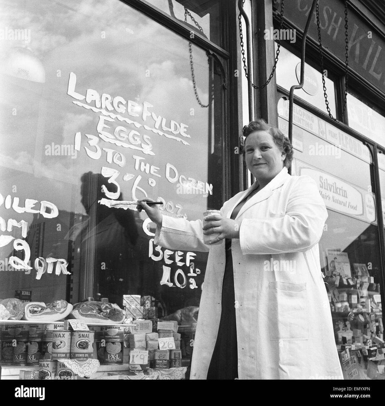 Norma Watson, manageress of a grocery shop in Sale, near Manchester repaints the egg sign on her shop window. The - Stock Image