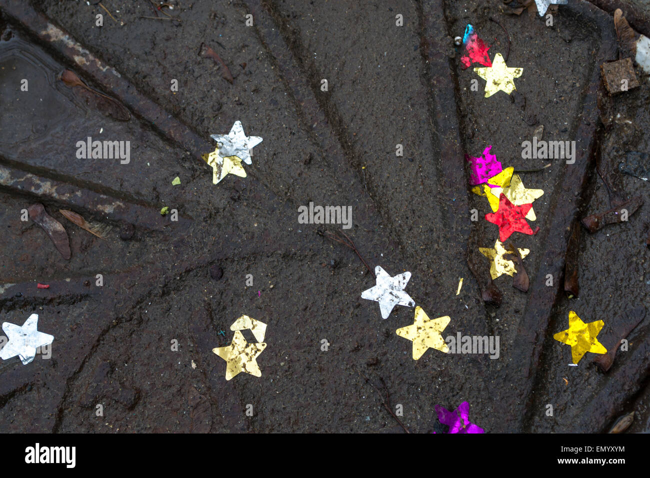 Colored stars in dirty water on top of a dark metal manhole cover - Stock Image