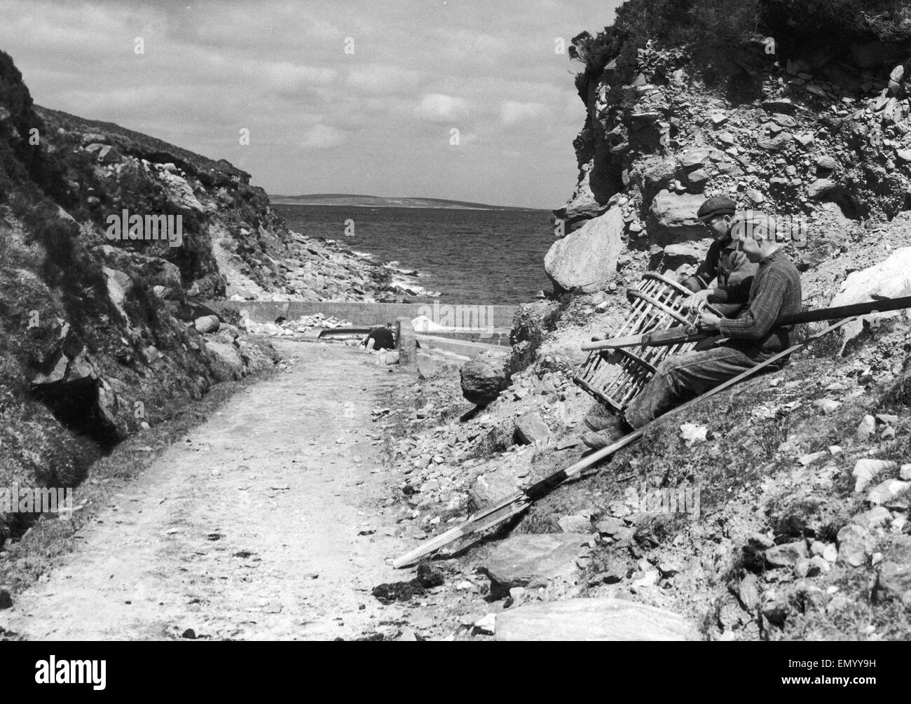 Fishermen seen here on Achill Island County Mayo Ireland repairing their lobster pots 20th June 1938 - Stock Image