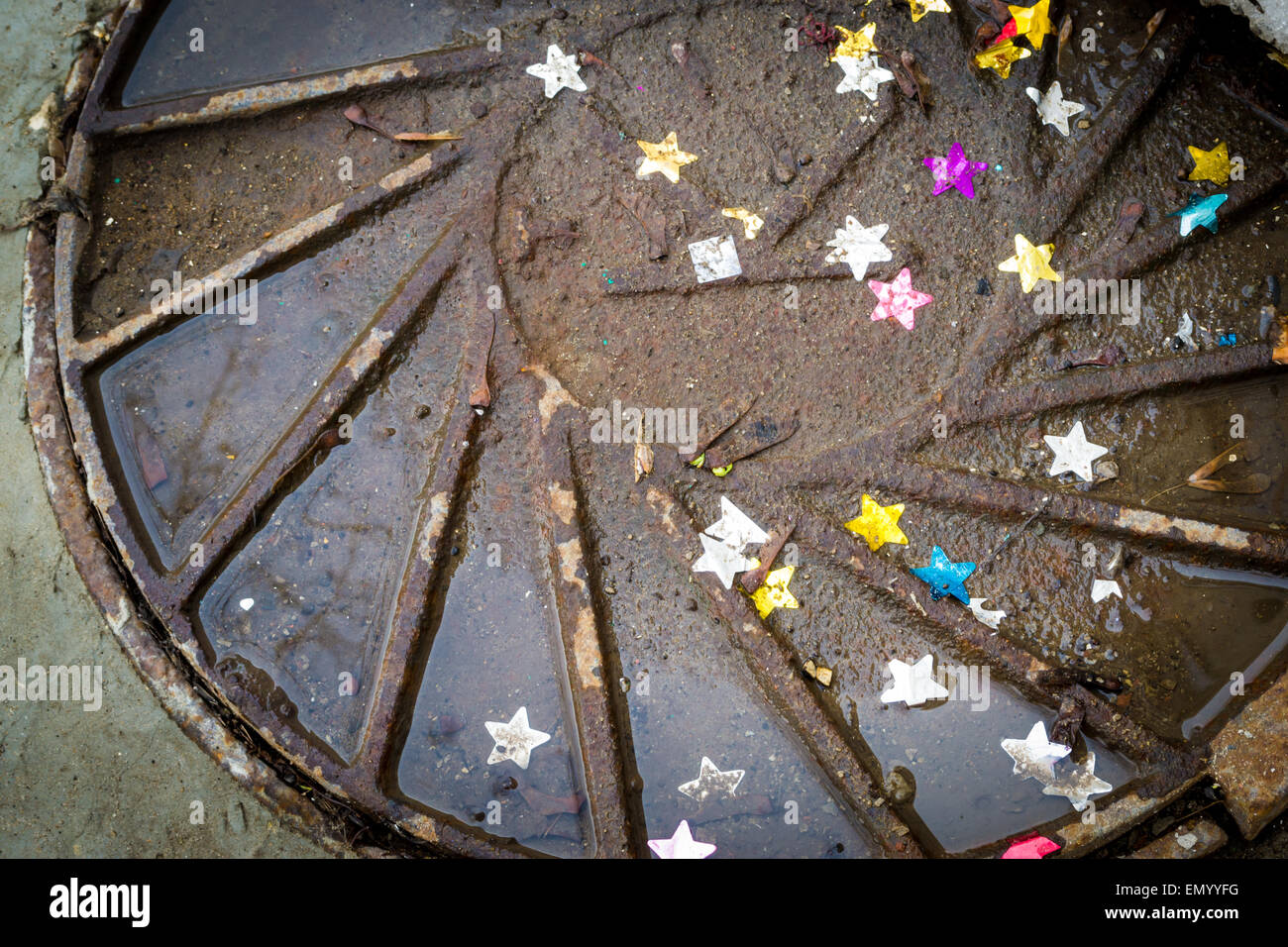 Multicoloured stars sink into a sewer manhole cover covered in rain - Stock Image