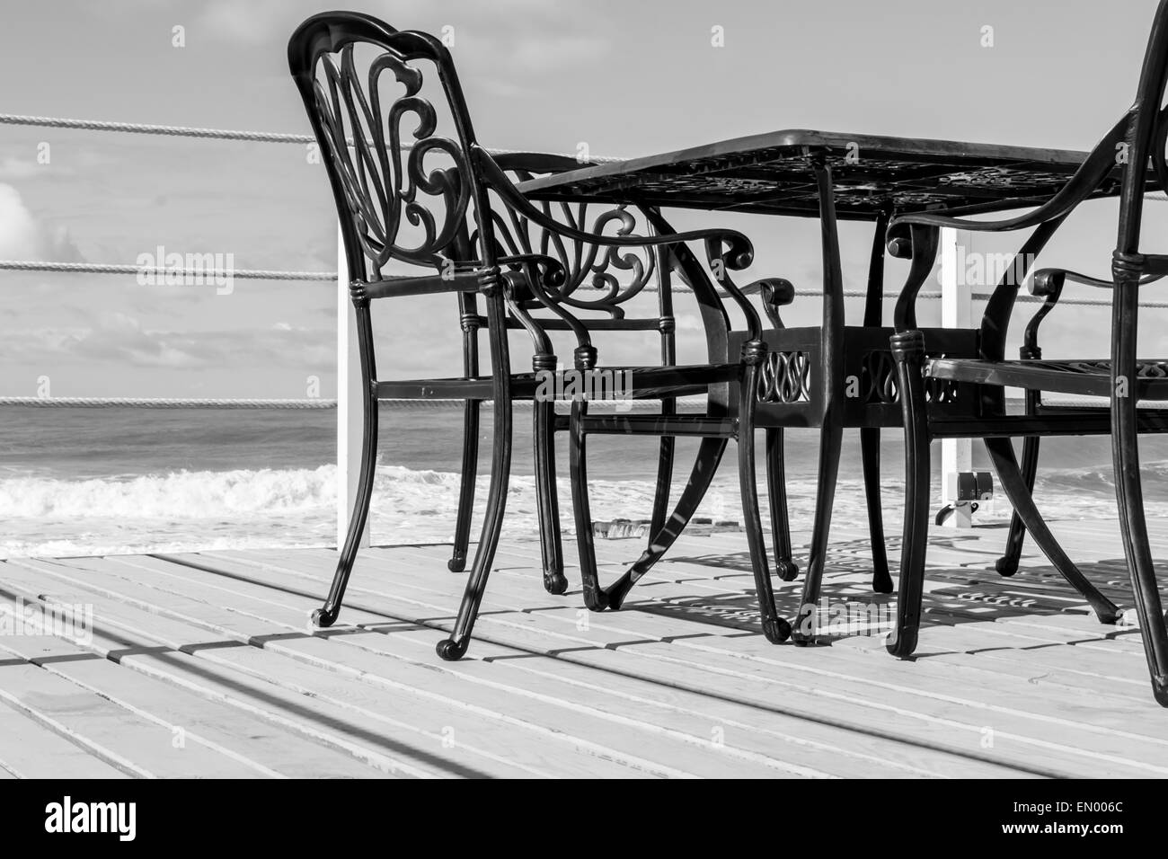 Empty Black Cast Iron Chairs And A Table On Wooden Planking   Stock Image