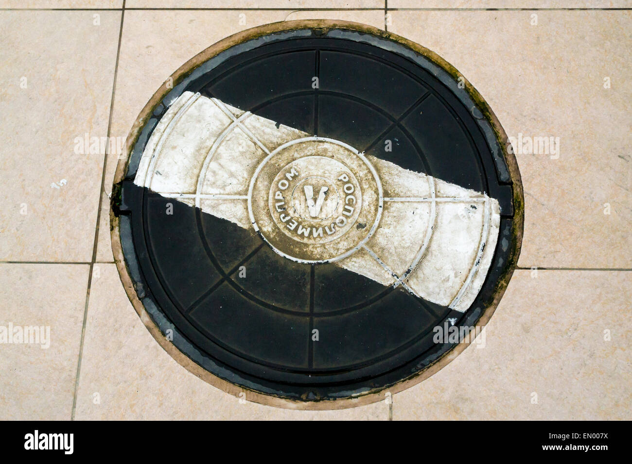 Black and White manhole cover on a tiled cemented walkway - Stock Image