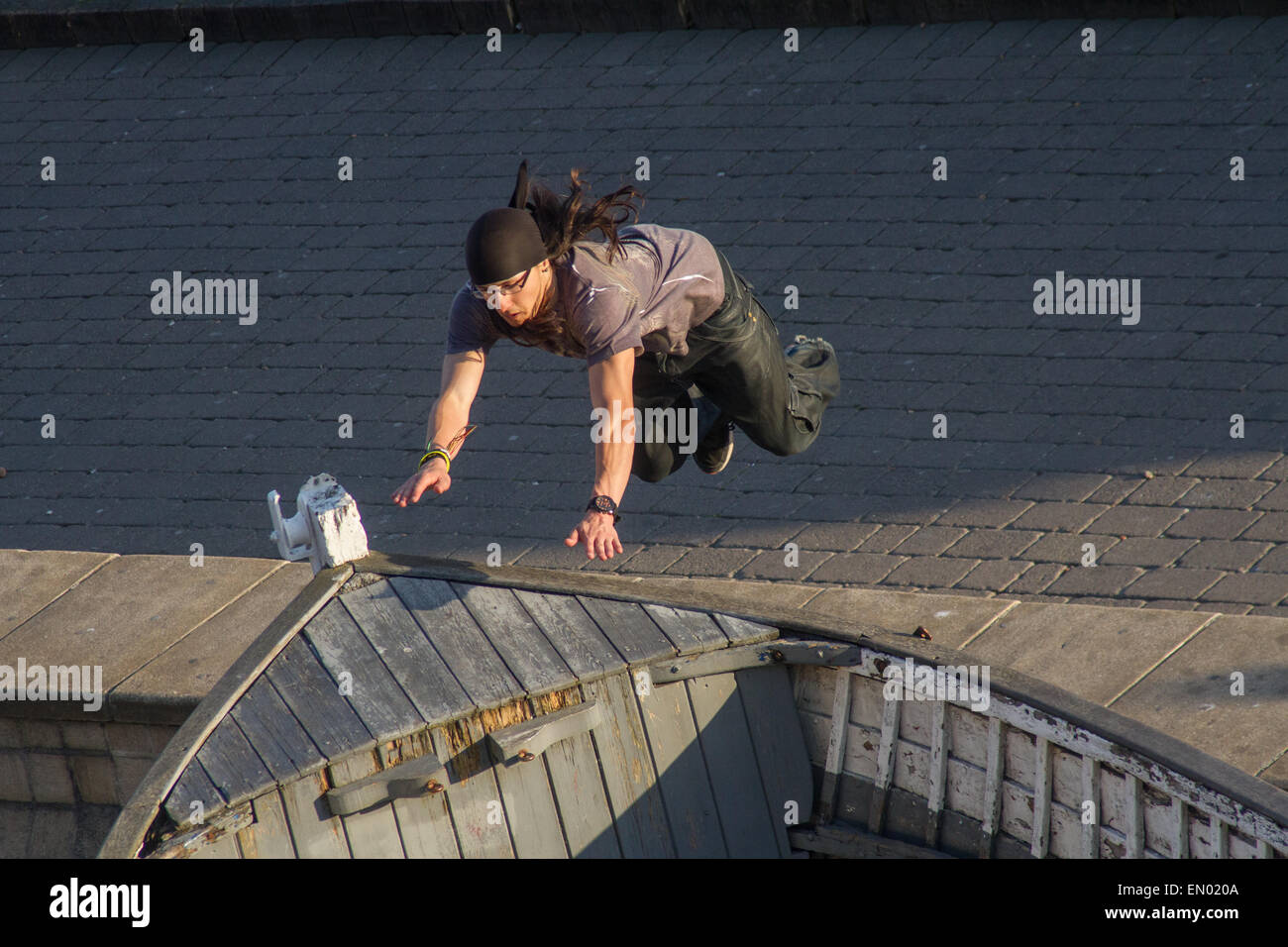 A man practises freerunning or parkour on to a boat on Brighton seafront - Stock Image