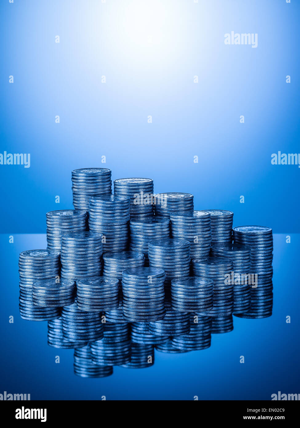 Stacks or piles of Swiss coins, two Francs pieces with reflection on shiny surface, blue gradient background, vertical - Stock Image