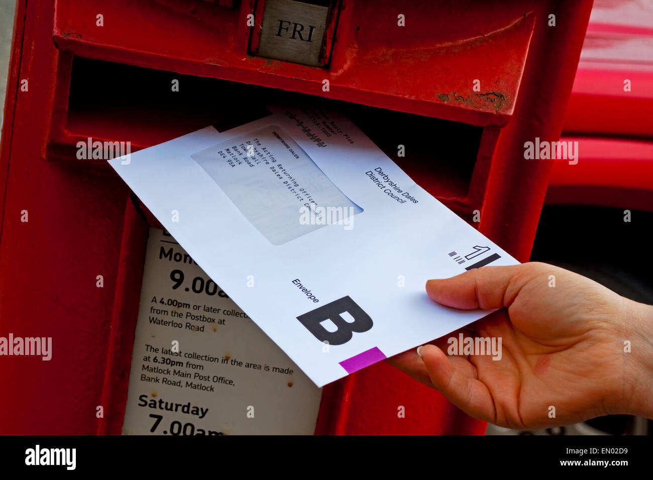 Person posting a UK postal vote ballot envelope for an election in a traditional British red pillar box Stock Photo