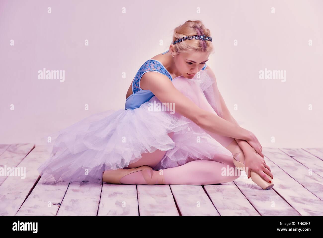 Tired ballet dancer sitting on the wooden floor - Stock Image