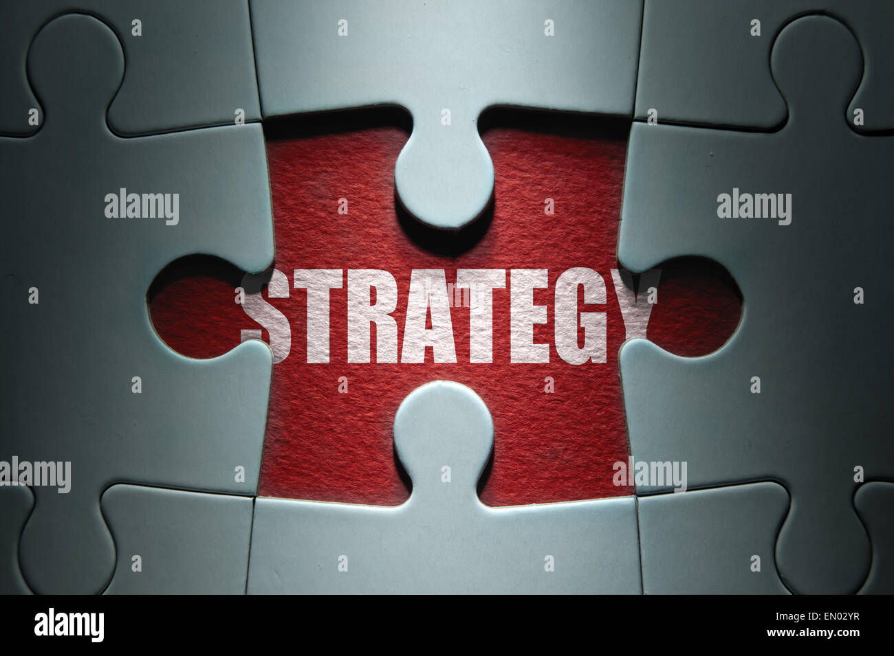 Missing piece from a jigsaw puzzle revealing the word strategy - Stock Image
