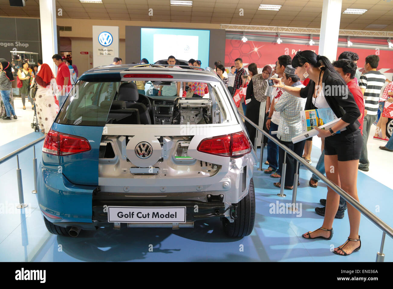 Gorgeous lady snaping picture of VW Golf cut model display at KL International Motorshow 2013. - Stock Image