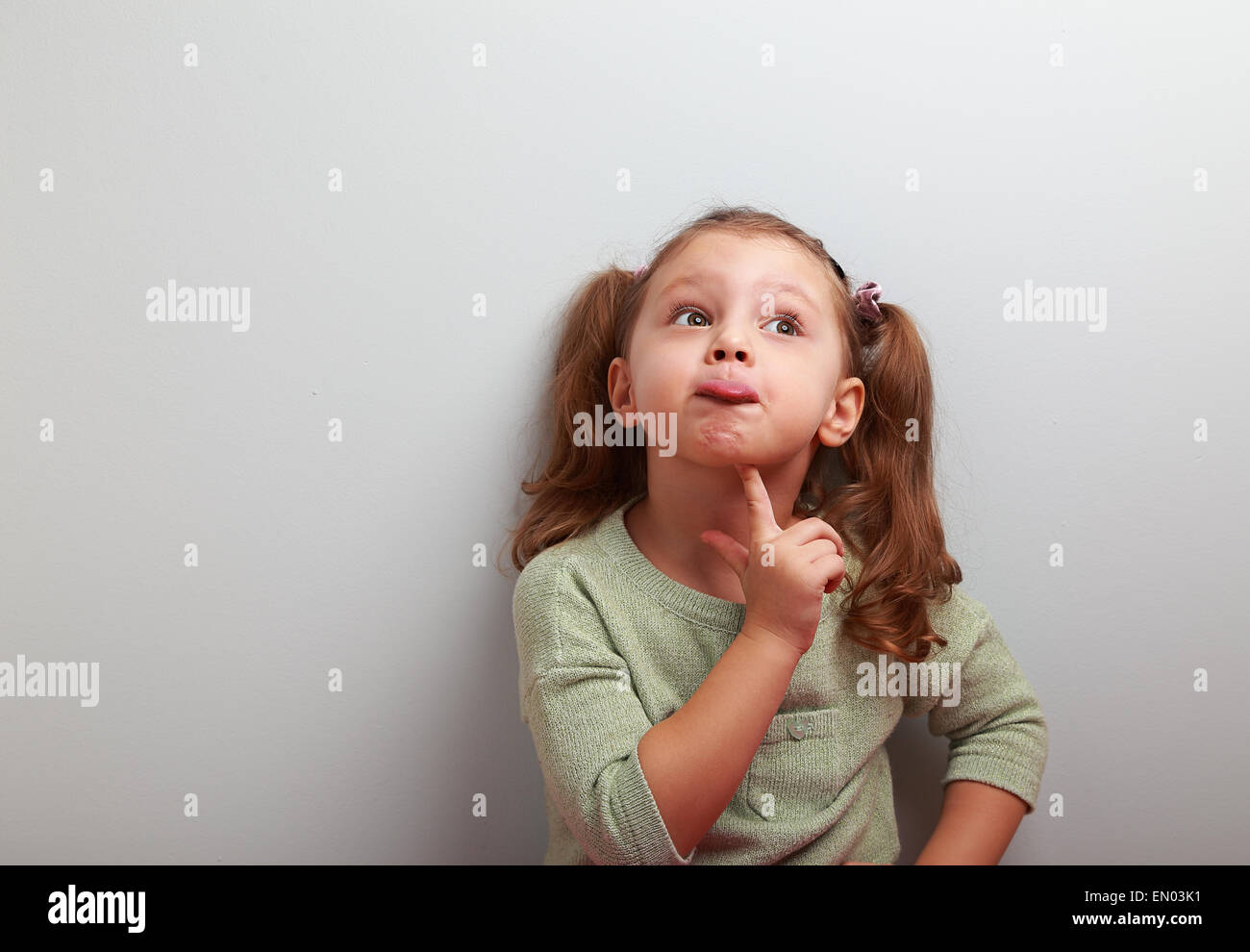 Fun grimacing girl thinking and looking up on blue background with empty copy space - Stock Image