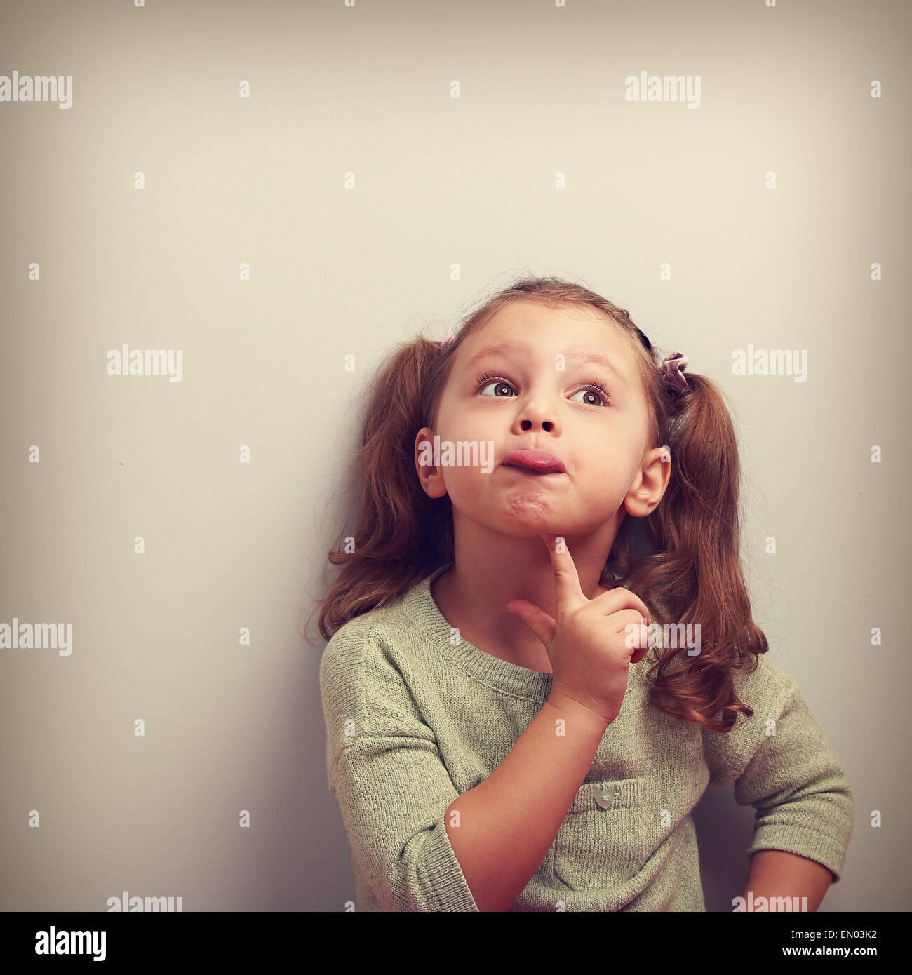Fun grimacing girl thinking and looking up. Square vintage portrait with empty copy space - Stock Image