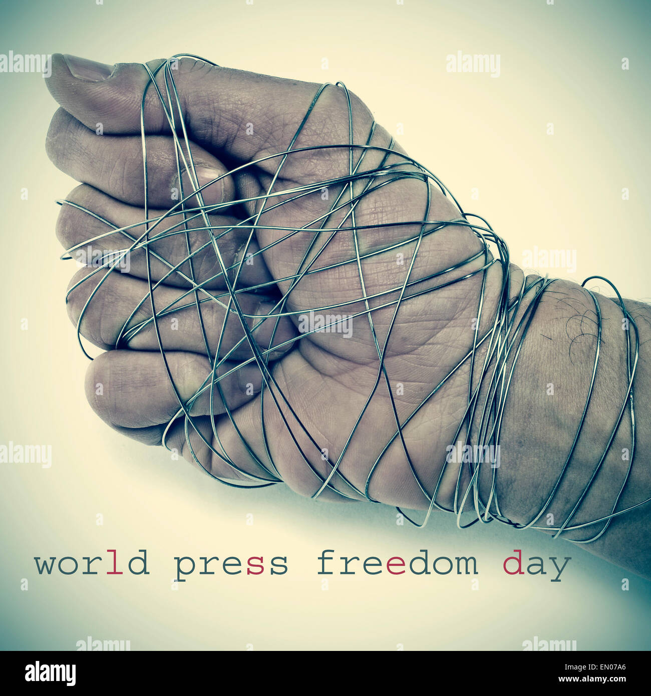 the text world press freedom day and the hand of a man completely tied with wire, depicting the idea of oppression - Stock Image