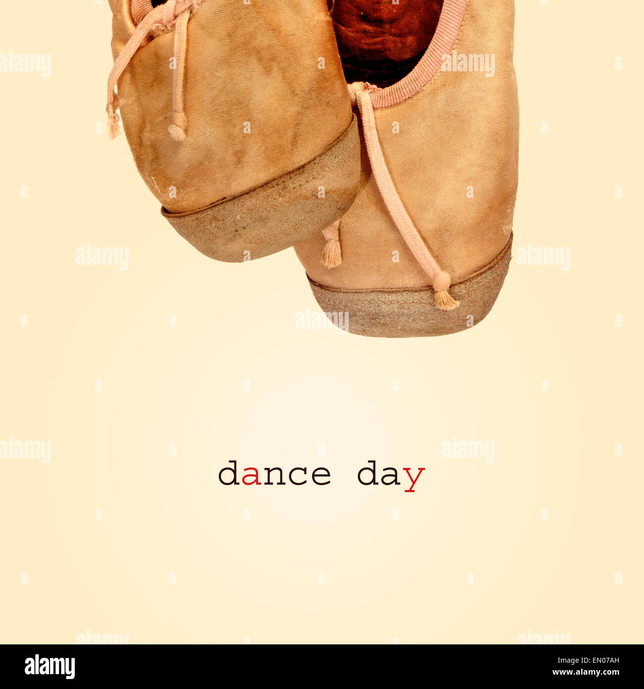 closeup of a pair of worn pointe shoes and the text dance day on a beige background, with a retro effect - Stock Image
